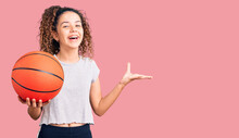 Beautiful Kid Girl With Curly Hair Holding Basketball Ball Celebrating Victory With Happy Smile And Winner Expression With Raised Hands