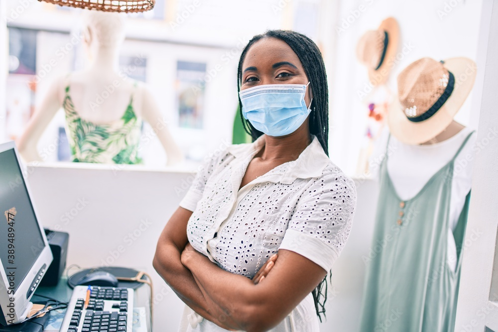 Fototapeta Young african american shopkeeper woman wearing medical mask working at clothing store