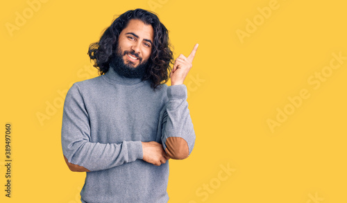 Fototapety, obrazy: Young arab man wearing casual clothes with a big smile on face, pointing with hand and finger to the side looking at the camera.