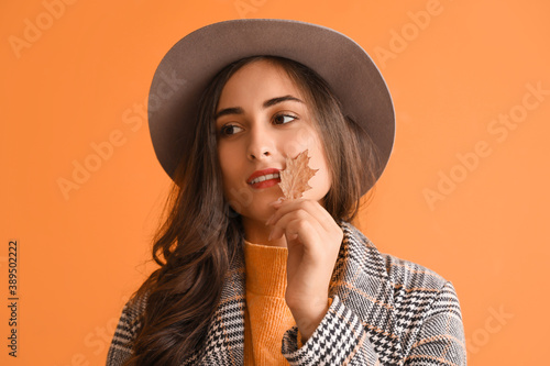 Fototapeta Stylish young woman with autumn leaf on color background