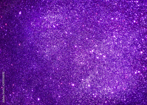Violet abstract sparkle background reminding starry night sky. Purple glitter texture of decoration material.