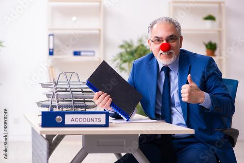 Fotografia, Obraz Old businessman clown working in the office