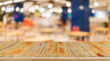 Fototapeta Kawa jest smaczna - Empty wood table top and blurred coffee shop and restaurant interior background - can used for display or montage your products.