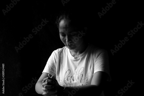 Valokuva Portrait of young woman kneeling and praying in silent prayer pose, on black and white background