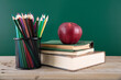 A stack of books with a red apple and a pen holder full of colored pencils in front of the blackboard