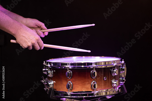 Photo Drummer hitting drumsticks on snare drum on black background close up