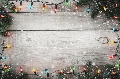 Cuadros en Lienzo Christmas background - Christmas lights bulb and fir branch and snowflake on rustic wood table, frame border design