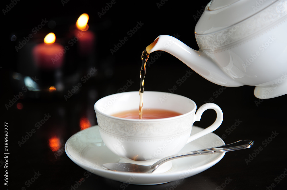 Fototapeta Process brewing tea,dark mood.The steam from hot tea is poured from the kettle into a kettle with tea leaves redcurrant mandarin orange lemon,rosemary, mint.,hot food and healthy meal concept
