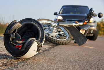 Photo of car, helmet and motorcycle on the road, the concept of road accidents.