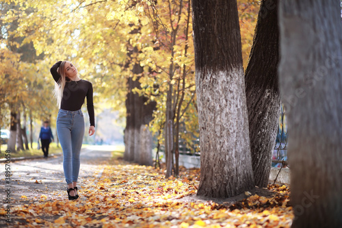 Young beautiful girl on a walk in the autumn park Canvas Print