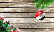 Concept Of New Year And Christmas, On A Wooden Background, Christmas Tree Branches And A Christmas Toy With The Flag Of Sealand,Principality Of.