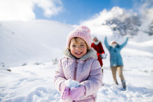 Portrait Of Cheerful Small Girl Playing In Snow In Winter Nature, Playing.