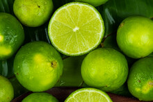 Close Up Pile Of Half And Whole Fresh Lime Juicy On Green Banana Leaves With Clearly Water Drop On Surface