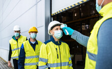 Group Of Workers With Face Mask In Front Of Warehouse, Coronavirus And Temperature Measuring Concept.