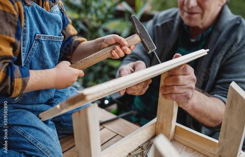 Fotografie, Obraz Unrecognizable small boy with senior grandfather constructing birdhouse, diy project