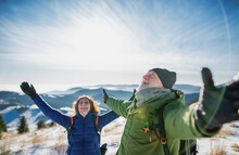 Senior Couple Hikers In Snow-covered Winter Nature, Stretching Arms.