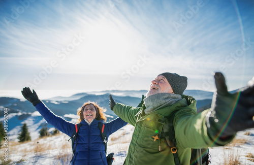 Senior couple hikers in snow-covered winter nature, stretching arms Fotobehang