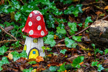 Artificial Childhood Display Of A Fly Agaric Red And White Wooden House Mushroom In An Enchanted Fairy Toadstool Woodland During The Autumn Fall Season Of November, Stock Image Photo