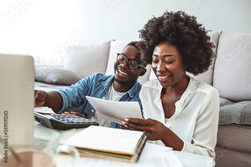 Family insurance concept. Positive black couple reading documentation at home, checking agreement details together. Young African Couple Sitting On Sofa Calculating Invoice
