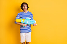 Photo Of Surprised Man Hold Water Gun Pistol Look Copyspace Wear Blue White Frock Isolated On Shine Yellow Color Background