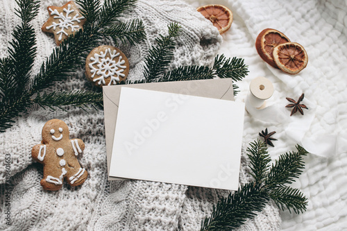 Christmas festive still life. Blank greeting card, invitation mockup and envelope on knitted sweater . Gingerbread cookies, dry oranges and fir branches on wool blanket. Selective focus, top view.