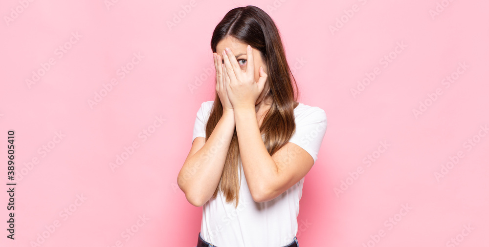 Fototapeta young pretty woman feeling scared or embarrassed, peeking or spying with eyes half-covered with hands