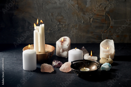 Tela occult science and supernatural concept - burning candles, stones and crystals f