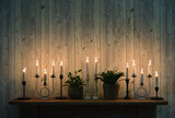 Burning vintage candles on wooden shelf against wooden wall background