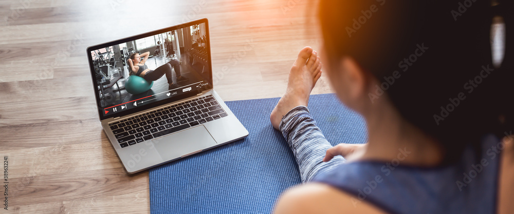 Fototapeta Young sporty woman in sportswear is sitting on the floor and watching online tutorials,Fitness training online on laptop during covid-19 or coronavirus outbreak at home in the living room.