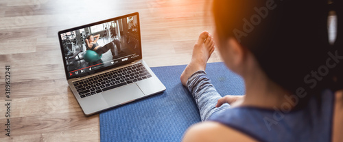 Fototapeta Young sporty woman in sportswear is sitting on the floor and watching online tutorials,Fitness training online on laptop during covid-19 or coronavirus outbreak at home in the living room. obraz