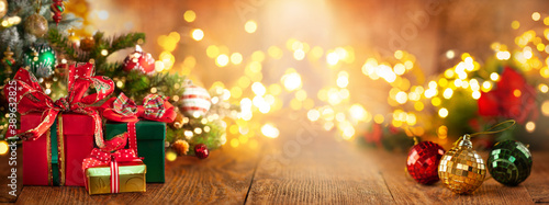 Christmas or New Year still life with Gift Boxes  and baubles below Christmas Tree on a wooden table Fotobehang