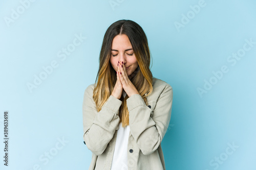 Foto Young caucasian woman isolated on blue background praying, showing devotion, religious person looking for divine inspiration