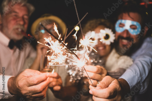 group of four people enjoying new year night celebrating with sparklers in the m Billede på lærred