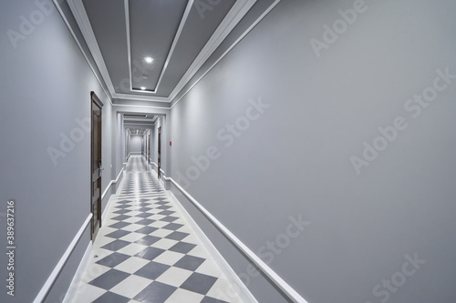 Photo Empty long gray corridor in hotel with closed doors