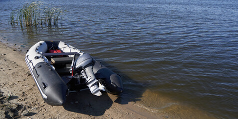 Inflatable boat with outboard motor on the sandy shore by river