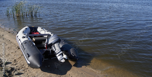 Vászonkép Inflatable boat with outboard motor on the sandy shore by river