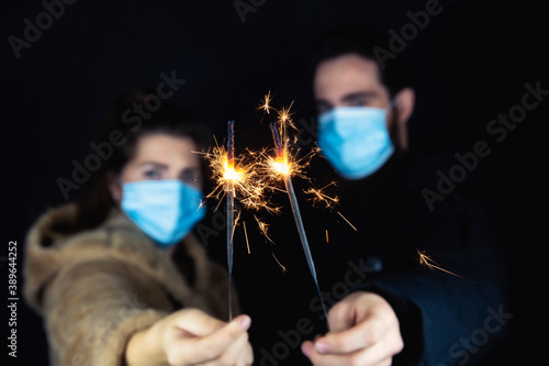 Obraz Young couple wearing protective face masks for Coronavirus and holding sparklers for New year's eve, 2021 and Covid-19 concept - fototapety do salonu
