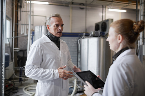Fotografia Waist up portrait of mature man instructing female worker while discussing work