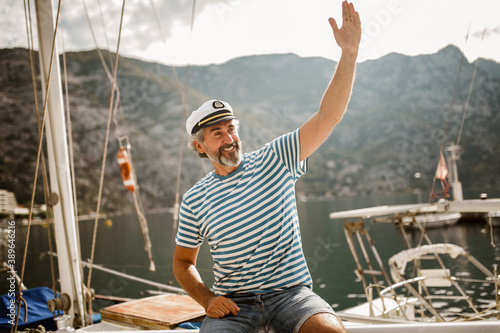 Leinwand Poster Mature man standing at helm of sailboat out at sea on a sunny afternoon