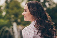 View From Bellow Of Beautiful Brunette With Curly Long Hair Smiling Laughing In Green Spring City Park Wearing Striped Shirt