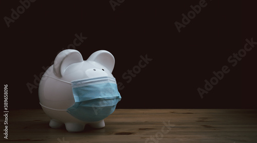 Fototapeta Piggy bank wearing surgical face mask. Global economy during coronavirus pandemic.  Financial crisis, banking concept. saving and investment. obraz