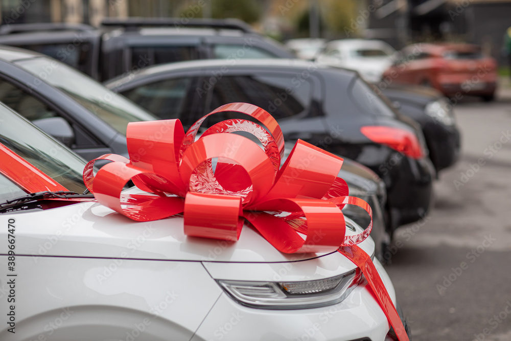 Fototapeta a white car with a big, red bow on the hood is on the street, an expensive gift, a new car as a gift, a gift car