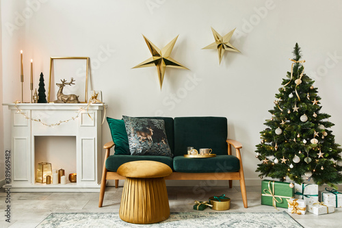 Obraz Stylish christmas living room interior with green sofa, white chimney, christmas tree and wreath, stars, gifts and decoration. Family time. Template. - fototapety do salonu