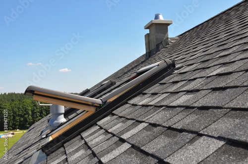 A gray roof covered with dimensional architectural asphalt shingles with an attic skylight, ventilation pipe, air duct and chimney Fototapet