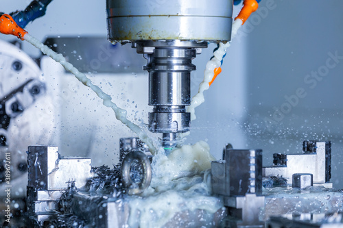 Foto vertical cnc steel milling process with external water coolant streams, splashes