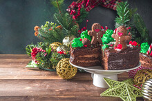 Christmas Chocolate Cake. Homemade Gingerbread Chocolate Cake With Sugar And Chocolate Decor In Form Of Xmas Traditional Symbols - Candy Cane, Gingerbread Man, Xmas Tree,