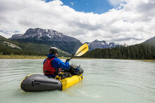 Man Paddling Yellow Raft Throu...