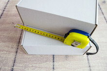 Measuring Box Concept. Cardboard Boxes And Tape Measure On A Wooden Background. Box Size