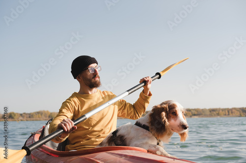 Cuadros en Lienzo Kayaking with dogs: man rowing a boat on the lake with his spaniel