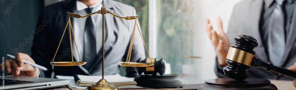 Fototapeta justice and law concept.Male judge in a courtroom on wooden table and Counselor or Male lawyer working in office. Legal law, advice and justice concept.